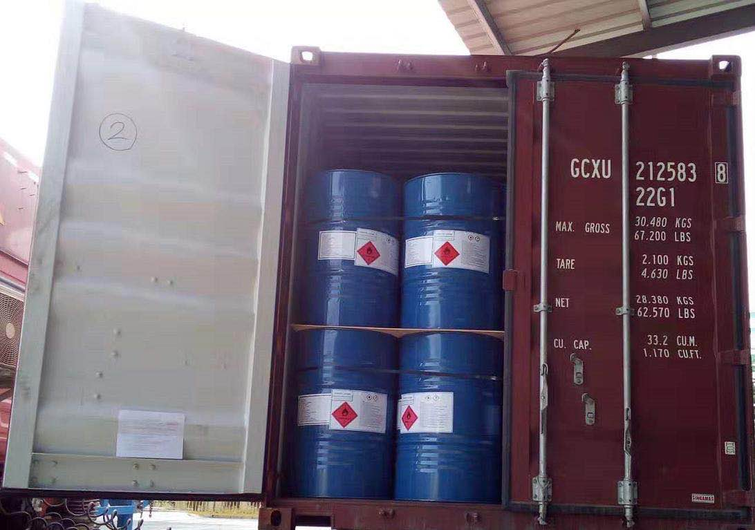 Steel drums of 99% isopropyl alcohol being loaded for export.
