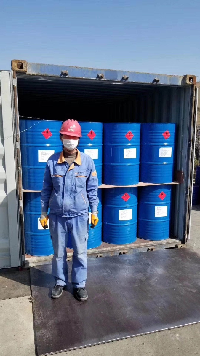 A Chinese factory worker standing next to isopropyl alcohol steel drums ready for export.
